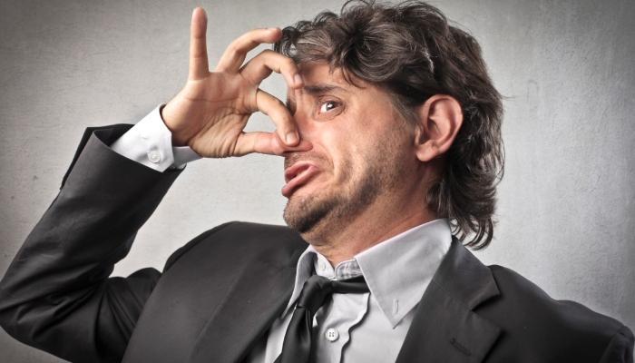 Мужчина зажимает нос пальцами